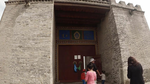 Tourists enter through the massive gates to the territory of the ancient monaste Footage