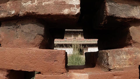 through an old red brick wall of a little seen Buddhist temple Footage