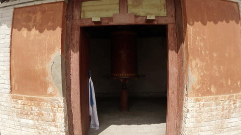 ancient Buddhist prayer wheel coil slowly turns in a doorway of an old temple Footage