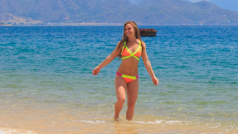 blond slim girl in bikini jumps swings in shallow sea Footage