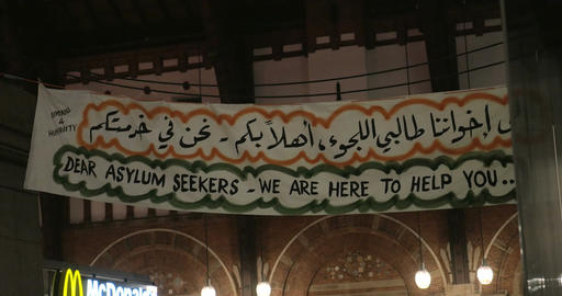 Banner Dear Asylum Seekers We Are Here to Help You in English and Arabic Script Live-Action