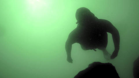 Freediver in a black wetsuit diving downwards towards the camera Footage