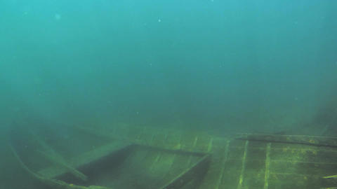 Sunken rowing boat fading into blue water Footage