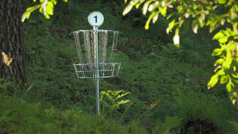 Disc golf basket number one with chains swaying slowly at a disc golf course Footage