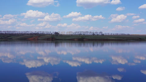 Clouds are reflected in smooth water of lake Footage