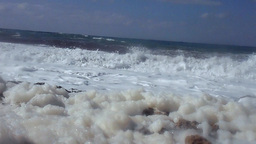 Waves rolling to the shore with foam in Cyprus, low angle Footage