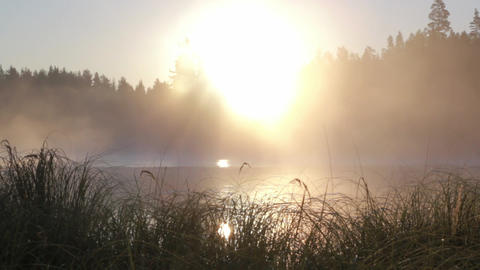 Panning shot of fog moving at a lake during sunrise Footage
