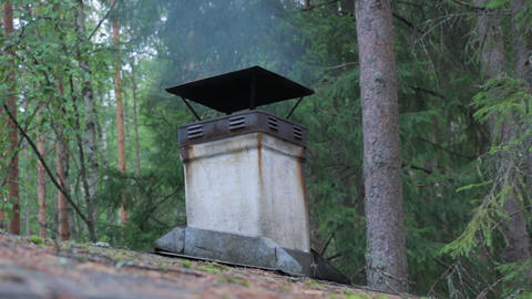 Smoke rising from a smokestack of an old wooden sauna Live Action