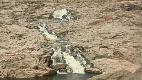 people relaxing near water cascade rocky barrier medium shot Footage