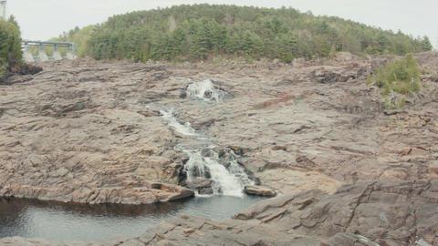 people relaxing near water cascade rocky barrier wide shot Footage