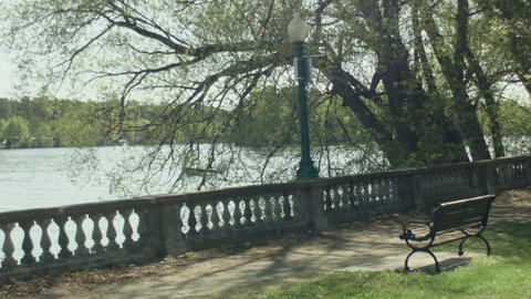 romantic sidewalk in front of a quiet lake motor boat passing by bench in front  Footage