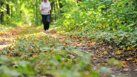 attractive woman running along path in park Footage
