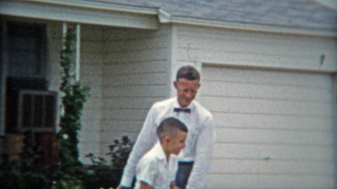1953: Dad and son playing basketball in driveway, formally dressed Footage