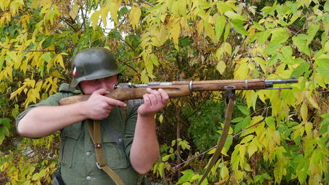 Wehrmacht soldier fires his rifle. Close-up Live Action