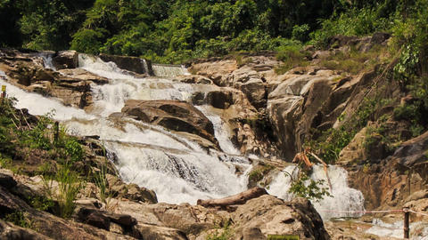 view of waterfall cascade among rocks in tropical park Footage