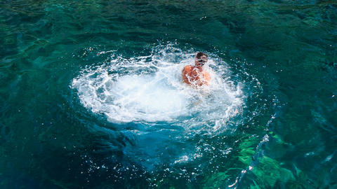 side view man makes high dive from boat into transparent sea Footage