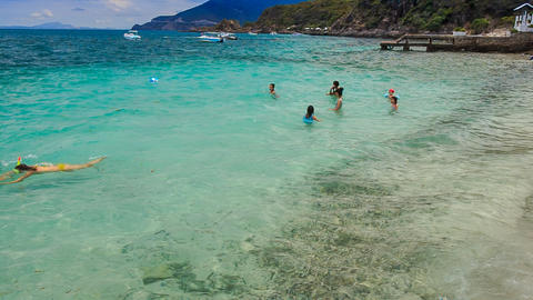 closeup tourists swim in transparent water by resort on island Footage