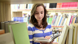 Dolly Shot Through Bookshelf Of Happy Student stock footage