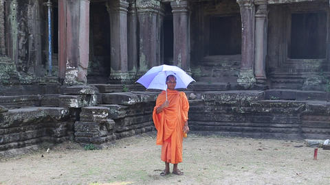 Buddhist monk in orange clothes with blue umbrella in Angkor Thom temple complex Footage