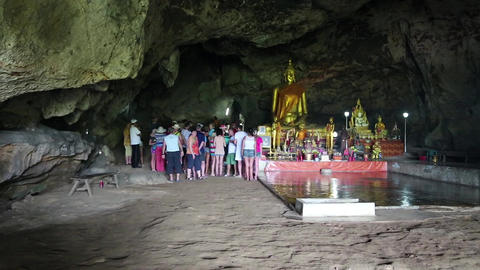 People and Golden Buddha statue inside temple in the cave, Thailand Footage
