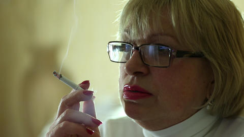 Senior woman with glasses smoking a cigarette, female smoker Footage