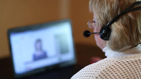 Woman with headphones on computer talks to a customer via computer Live Action
