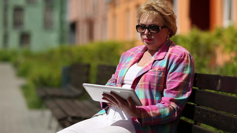 Woman sits on the bench and uses tablet computer. Woman with tablet computer Footage