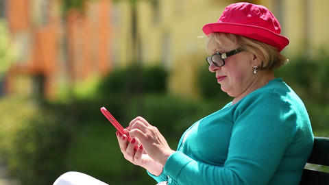 Woman sits on the bench and uses smartphone Footage