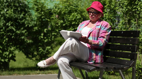 Woman sits on the bench and uses tablet computer. Woman with pad Footage
