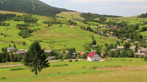 Beautiful green hills and cottage with red roof in village Footage