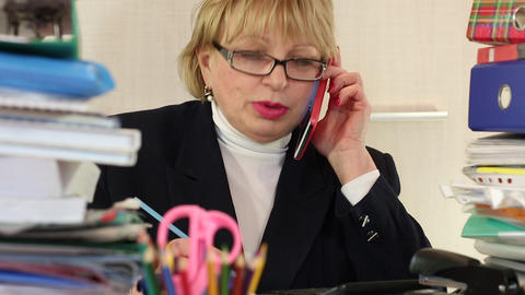 Senior woman chief accountant in glasses and with red smartphone Live Action