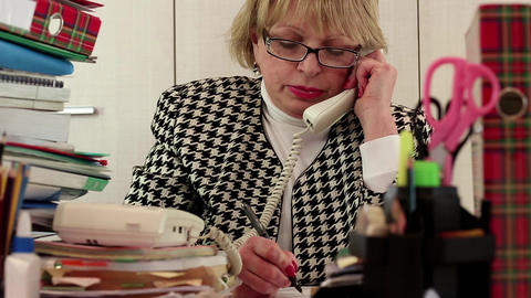 Senior woman chief accountant in glasses and with telephone Live Action