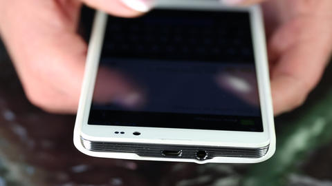 Closeup of woman hands with white smartphone. Woman typing sms on her cell phone Footage