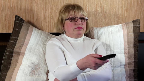 Woman with remote control sits on the bed and switching tv channels Footage