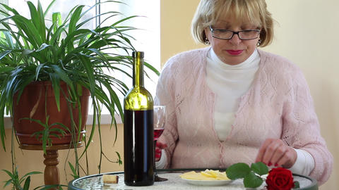 Woman sits at a table drinking red wine and eating cheese Footage