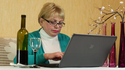 Woman with a bottle of wine sitting at the table and types text using notebook Footage