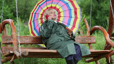 Woman with umbrella sits on the swing bench and communicates via cell phone Footage