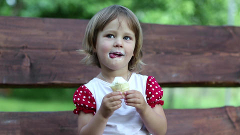 Little girl sits on the swing bench and eats ice cream Footage