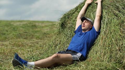 Man lying on a haystack, stretching oneself, breathing deep Footage