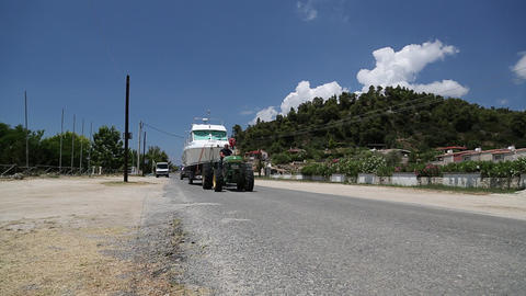 Green wheeled tractor transporting the boat on a paved road Footage