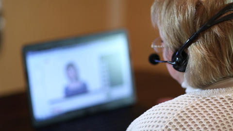 Woman with headphones on computer talks to a customer via computer Footage