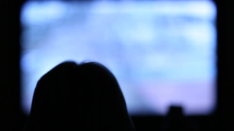 Woman with remote control switching tv channels Footage