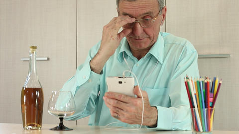 Man with smartphone sits at a table Footage