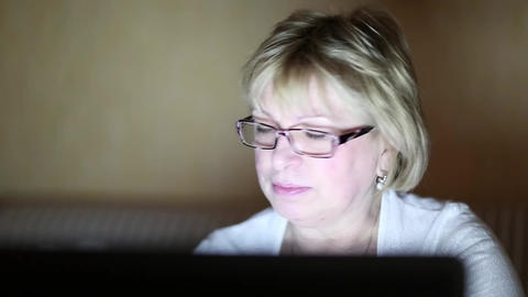 Woman with laptop in a dark room Footage