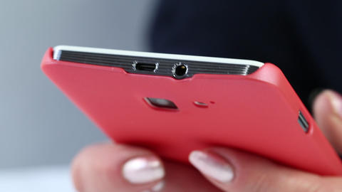 Closeup of woman hands with red smartphone. Woman typing sms on her cell phone Live Action