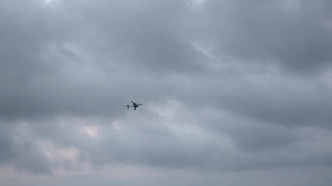 Distant plane crosses the cloudy sky Footage