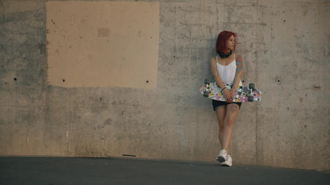 Tattooed red head woman stands in a concrete wall with his skateboard Footage