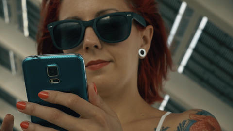 Tattooed woman using a smart phone with a big solar panel Footage