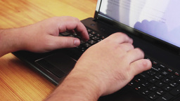 Hands typing text on notebook