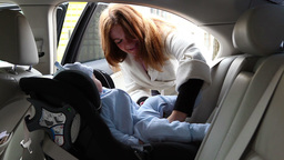Mother Put Child in Safety Carseat Stock Video Footage